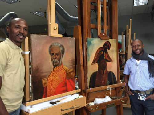Erntz Jeudy (L) and Racine Joseph (R) with portraits of Nissage Saget and Henri Christophe by Haitian artist Louis Rigaud