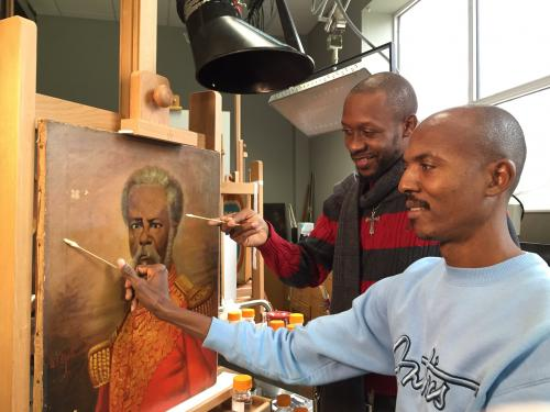 Racine Joseph (L) and Erntz Jeudy (R) surface cleaning a painting by Haitian artist Louis Rigaud